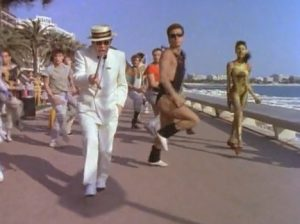 Elton John Still Standing dancing on the beach